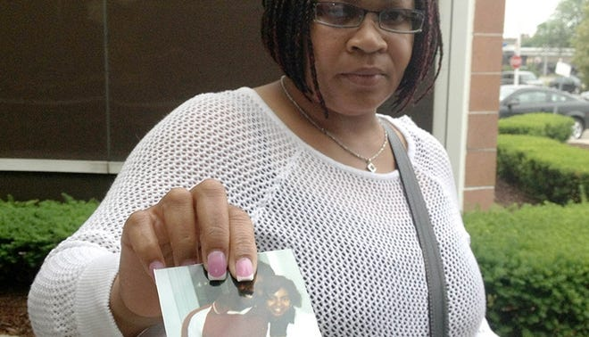 Roda Wright, 41, of Detroit, holds a picture of her mother, Faye Elizabeth Wright, who disappeared Oct. 3, 1991, while walking on Detroit's east side.