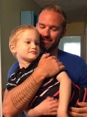 Eric Mehl, of Carmel, Ind., was recently named one of the nine hottest dads in America by NBC and iVillage. He won in the 'Hottest Tattooed Dad' category; the tattoo on his forearm is his son's name in Kryptonian (language from Superman).