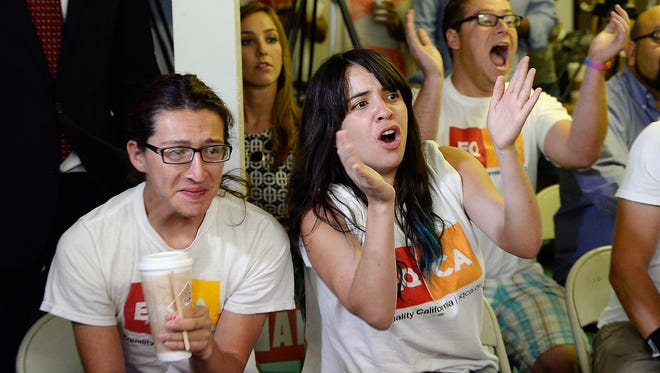 Jesse Quintalla, left, 28, and Jessica Parral, 24, react to the Supreme Court ruling at a watch party at Equality California, a non-profit civil rights organization that advocates for the rights of LGBT people in California.