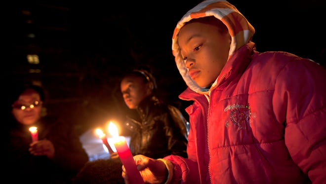 """Children and their family hold candles and sing the song """"Amazing Grace"""" to show their support at night outside the entrance to the Mediclinic Heart Hospital where former South African President Nelson Mandela is being treated in Pretoria, South Africa, June 26."""