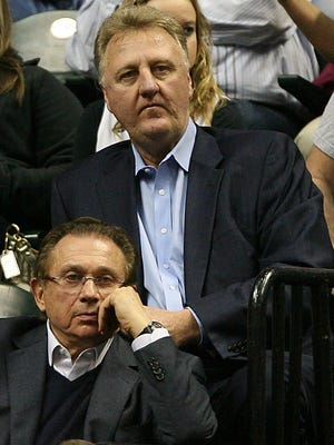 Larry Bird, sitting in front of Pacers owner Herb Simon, will return to the helm for Indiana.