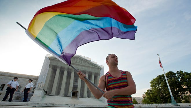 A gay rights advocate waves a rainbow flag in front of the Supreme Court in Washington.
