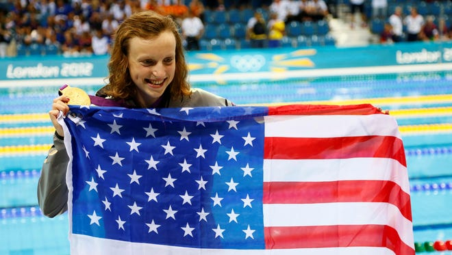 In a file photo from Aug 3, 2012, Katie Ledecky poses with her gold medal and an American flag after winning the women's 800 freestyle final during the London Olympics.