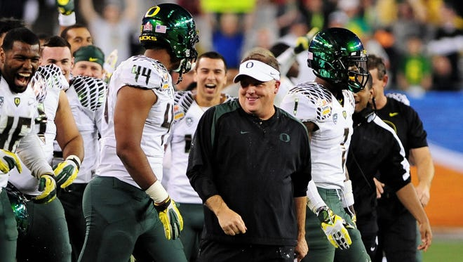 Oregon coach Chip Kelly smiles on the field after defeating the Kansas State in the Fiesta Bowl at University of Phoenix Stadium. The game was Kelly's last with the Ducks.