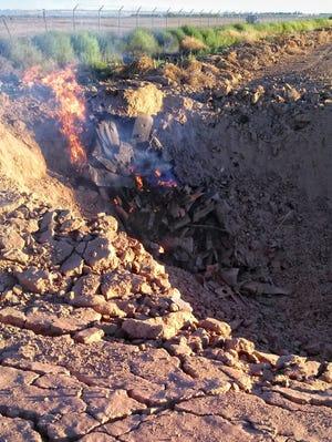 Debris burns at the scene of a F-16 crash June 26, 2013, at Luke Air Force Base in Glendale, Ariz.