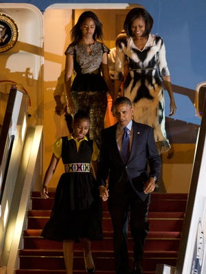 President Obama, Mrs. O. and daughters Sasha, front left, and Malia, descend from Air Force One as they arrive in Dakar, Senegal on Wednesday.