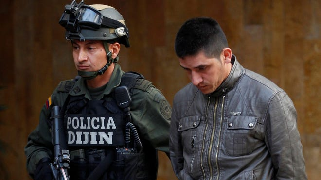 """Alleged gang member Edgar Murillo, arrested along with  other men in connection with the murder of U.S. DEA Special Agent James """"Terry"""" Watson at police headquarters in Bogota, Colombia."""