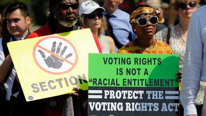 Supporters of the Voting Rights Act listen to speakers discussing today's rulings outside the U.S. Supreme Court building.