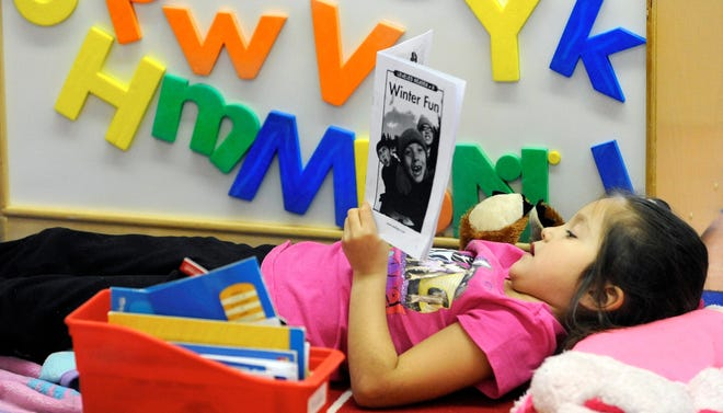 Wadewitz Elementary School kindergarten student Analisa Sanchez reads in class Feb. 1, 2012, in Racine, Wis. Students in her class count all the books they read in class and at home and report their totals to the Racine Reads Program.