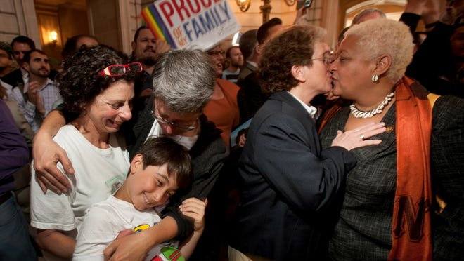 Sue Rochman, left, and Robin Romdalvik hug their son, Maddox Rochman-Romdalvik, 8, at San Francisco's City Hall on Wednesday.