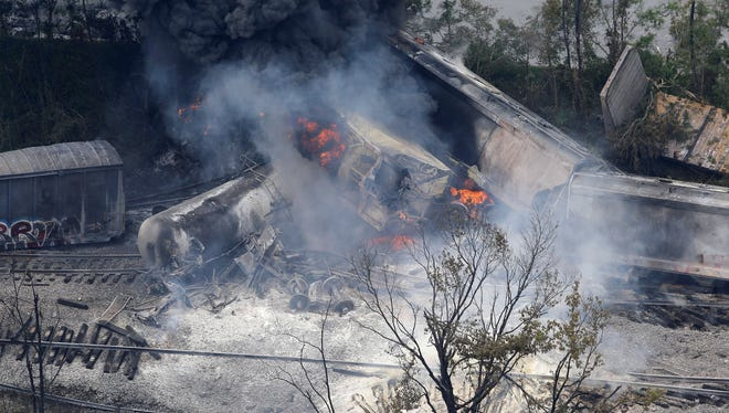 A fire burns at the site of a CSX freight train derailment, May 28, in Rosedale, Md., where fire officials say the train crashed into a trash truck.