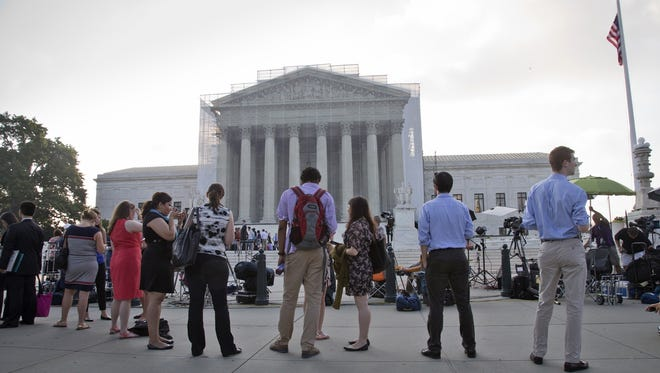 People wait outside the Supreme Court in Washington as key decisions on the Voting Rights Act are handed down.