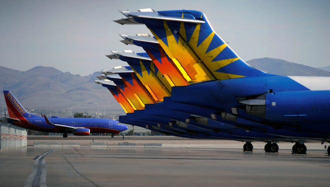 A Southwest jet taxis by parked Allegiant Air planes at McCarran International Airport in Las Vegas.