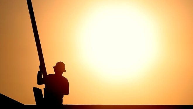 A construction worker is shown atop a roof at sunrise to beat daytime high temperatures, Thursday, in Queen Creek, Ariz.