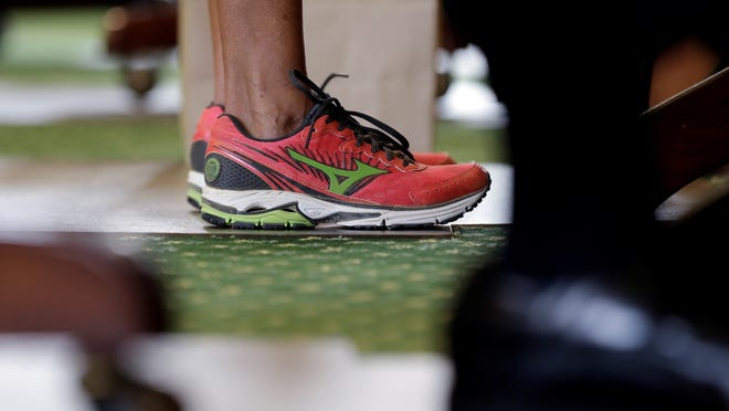 Sen. Wendy Davis, D-Fort Worth, wears tennis shoes in place of her dress shoes as she begins a one-woman filibuster in an effort to kill an abortion bill, Tuesday in the Texas senate chamber.