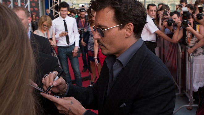 Johnny Depp signs autographs  as he arrives for 'The Lone Ranger' premiere in Moscow on Thursday.
