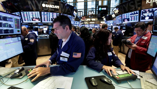 Specialists David Haubner and Wingszi Cihang work on the floor of the New York Stock Exchange Friday. Consumer sentiment levels were near a six-year high according to a University of Michigan poll released Friday, but the stock market got off to a slow start.
