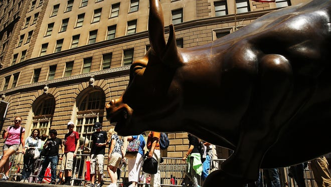 People wait in line to take a picture with the bronze bull in the Financial district on Wall Street in New York City.