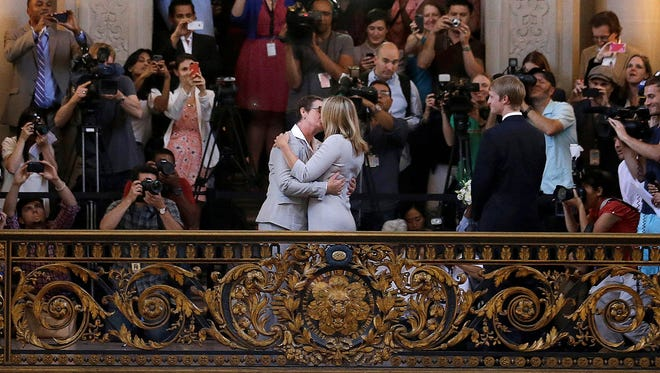 Kris Perry, foreground left, kisses Sandy Stier as they are married at City Hall in San Francisco, Friday.