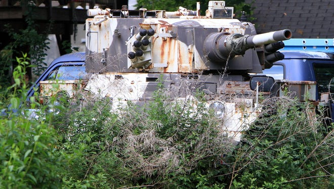 A full-sized British amphibious tank sits in the weeds behind the Orser home in Mahopac, N.Y., on Friday June 28.