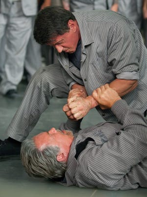 """Sylvester Stallone is on top of this fight with Arnold Schwarzenegger in a scene from """"Escape Plan."""""""