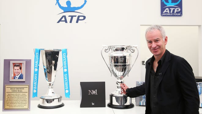 Former No. 1 John McEnroe poses with the newly named Brad Drewett Trophy and the ATP World Tour No. 1 trophy.