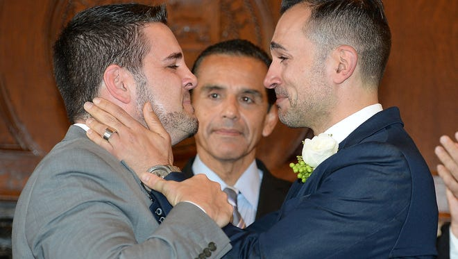 Paul Katami (L) and(R) react after they are married by Los Angeles Mayor Antonio Villaraigosa (C) at Los Angeles City Hall June 28, 2013.  Katami, Zarrillo and the other two plaintiffs in the U.S. Supreme Court case that overturned California's same-sex marriage ban were married June 28, after a federal appeals court freed gay couples to obtain marriage licenses in the state for the first time in 4 1/2 years.   AFP PHOTO / ROBYN BECKROBYN BECK/AFP/Getty Images ORG XMIT: 171702052 ORIG FILE ID: 520981953