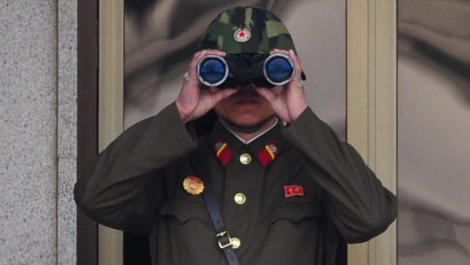 A North Korean soldier looks at South Korea across the Korean Demilitarized Zone (DMZ), on April 23, 2013, in Panmunjom, South Korea.