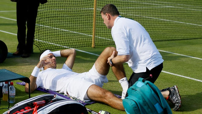 Juan Martin Del Potro of Argentina receives treatment after crashing into the umpire's chair during his victory against Grega Zemlja of Slovenia.