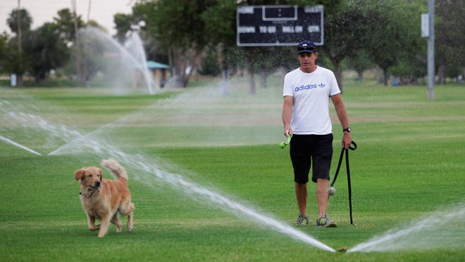 Chris Jolley, right, of Scottsdale, Ariz., runs his dog Logan through sprinklers at a local park on Saturday to try to beat the intense heat.