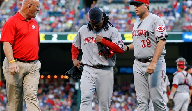 Cincinnati Reds pitcher Johnny Cueto leaves the game with pitching coach Bryan Price and a team trainer during the second inning against the Texas Rangers at the Rangers Ballpark in Arlington.