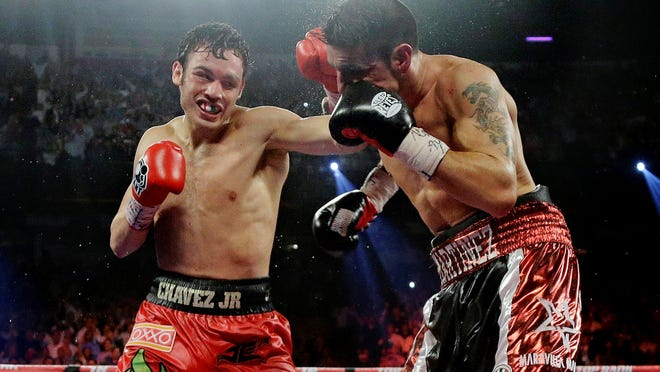 Julio Cesar Chavez Jr., left, shown against Sergio Martinez in their WBC middleweight title last September, had his fine for testing positive for marijuana slashed to $100,000.