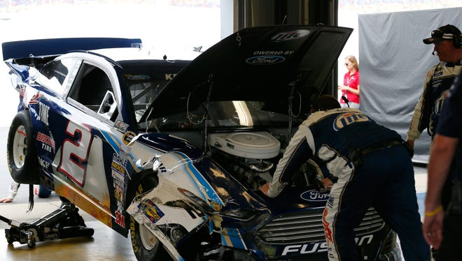 Crew members work on the No. 2 Ford of Brad Keselowski after a wreck on lap 48 of the Quaker State 400 at Kentucky Speedway.