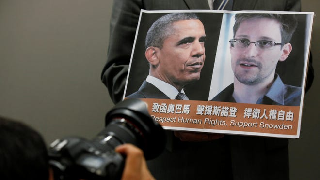 Photo of President Obama and Edward Snowden held by a protester in Hong Kong on June 14.