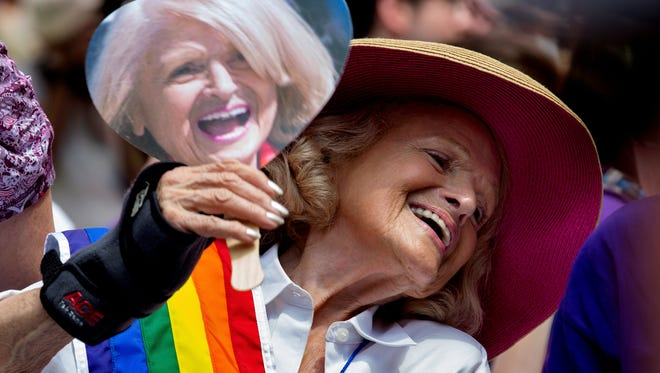 Edith Windsor, 84, the woman at the center of the U.S. Supreme Court decision granting gay couples federal marriage benefits, cools herself with a fan showing her image during the gay pride march in New York on Sunday.