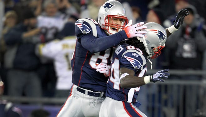 New England Patriots wide receiver Deion Branch (84), front, and New England Patriots tight end Aaron Hernandez (85) celebrate a Patriots touchdown in first half of a game against the Indianapolis Colts in 2010.