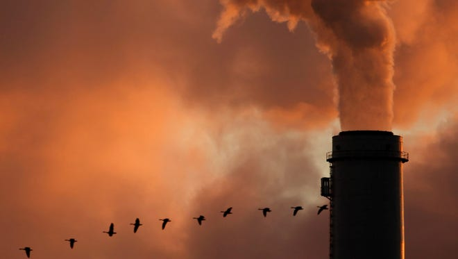 A flock of geese fly past a smokestack at a coal power plant.