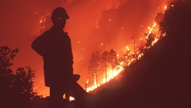 A firefighter watches the fire climb the Mogollon Rim above author Zane Grey's cabin in the 1990 Dude Fire east of Payson, Ariz.