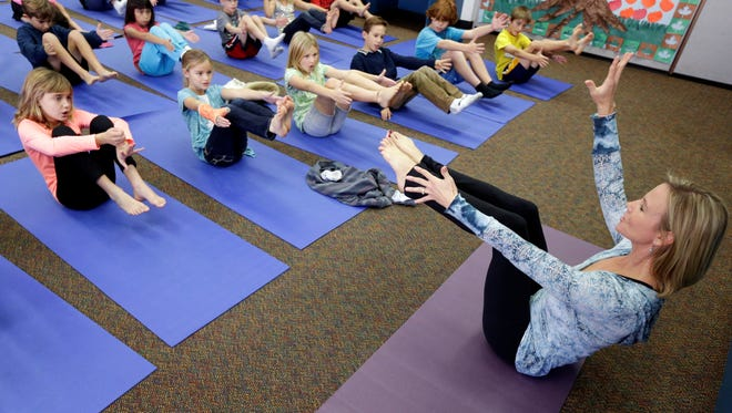 Yoga instructor Kristen McCloskey, right, leads a class of third graders at Olivenhain Pioneer Elementary School in Encinitas, Calif.