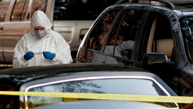 A New York City crime scene investigator examines fingerprints taken from a stolen sports utility vehicle in Brooklyn, N.Y., on July 9, 2007.