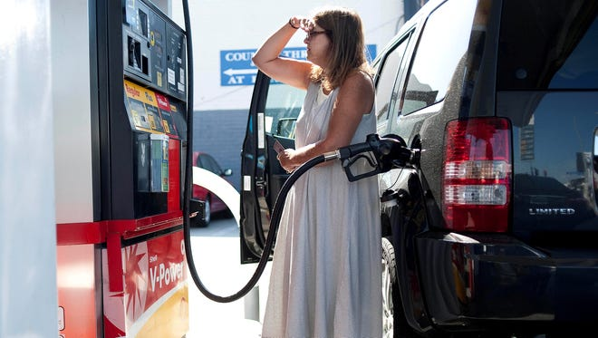 Teresa Jones watches the pump as she puts gas into her car at a Shell station on Pico Blvd in Los Angeles in this 2012 file photo.
