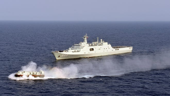 China's amphibious ship Jinggangshan is seen during a coordination training with a hovercraft in waters near south China's Hainan Province, in the South China Sea in March 2013.