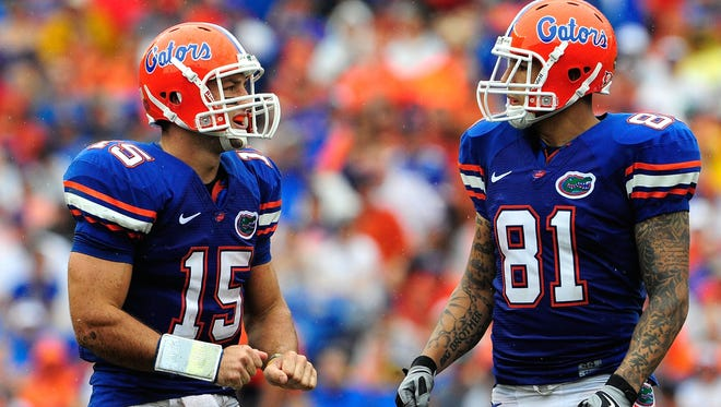 In this photo, Tim Tebow #15 of the Florida Gators speaks with Aaron Hernandez #81 during the game against the Troy Trojans  at Ben Hill Griffin Stadium on September 12, 2009 in Gainesville, Florida.  A police report says Tebow tried to keep Hernandez out of a bar fight in 2007.