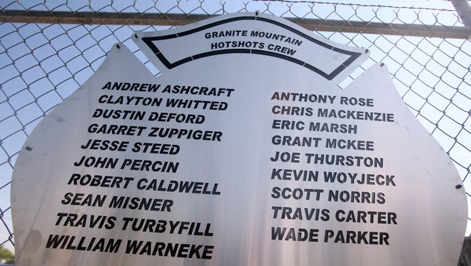 A plaque engraved with names of the 19 fallen firefighters is mounted on a fence July 2, 2013, outside of Granite Mountain Hotshots Fire Station 7 in Prescott, Ariz.