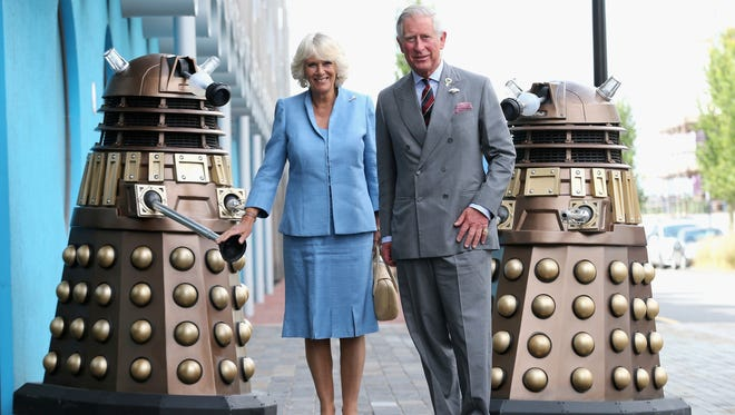Prince Charles and his wife, Camilla Duchess of Cornwall, pose next to Daleks during visit to 'Doctor Who' set in Wales.