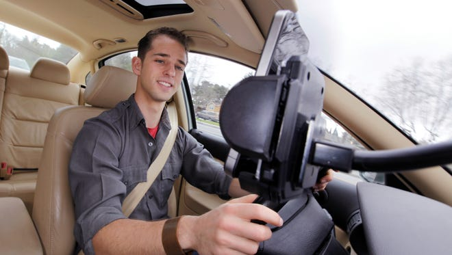 In this file photo, Ben Gleitzman uses traffic and navigation app Waze as he drives to work in Menlo Park, Calif.