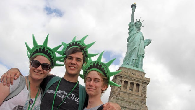 From left, Jess Burns, Zach Jamison and Nathan Mulls pose in front of the Statue of Liberty while on holiday from Australia on July 4, 2013. The Statue of Liberty reopened months after Superstorm Sandy hit the island.