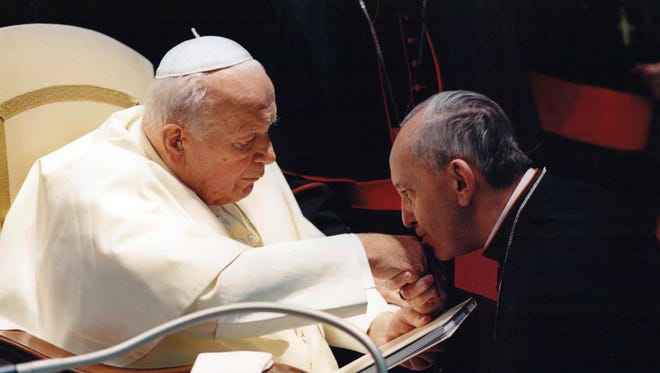 Jorge Mario Bergoglio, Archbishop of Buenos Aires, right, kisses the hand of Pope John Paul II during a ceremony at the Vatican. Bergoglio, who became Pope Francis on March 13 cleared Pope John Paul II for sainthood, approving a miracle attributed to his intercession.