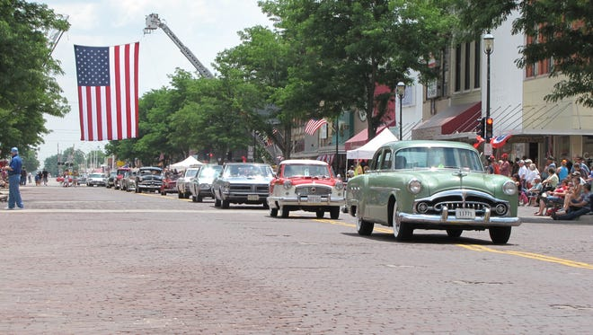 A parade of vintage cars and trailers cruise down Kearney's main street in a centennial salute to the Lincoln Highway.