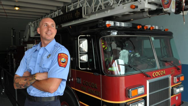 Cocoa Fire Department firefighter Matt Holladay stands next to the truck he rode to a recent house fire in which he rescued a woman.
